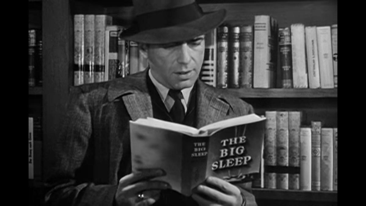 Humphrey Bogart reading a copy of The Big Sleep by Raymond Chandler