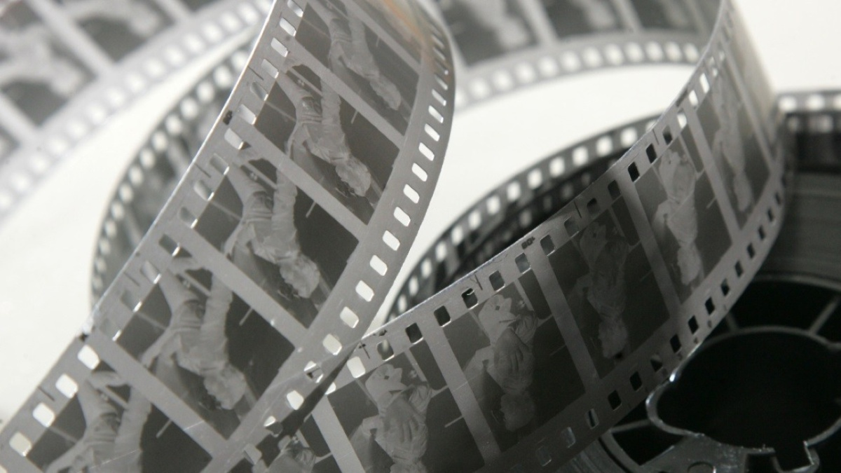 Black and white photograph featuring a reel of 35mm film stock.