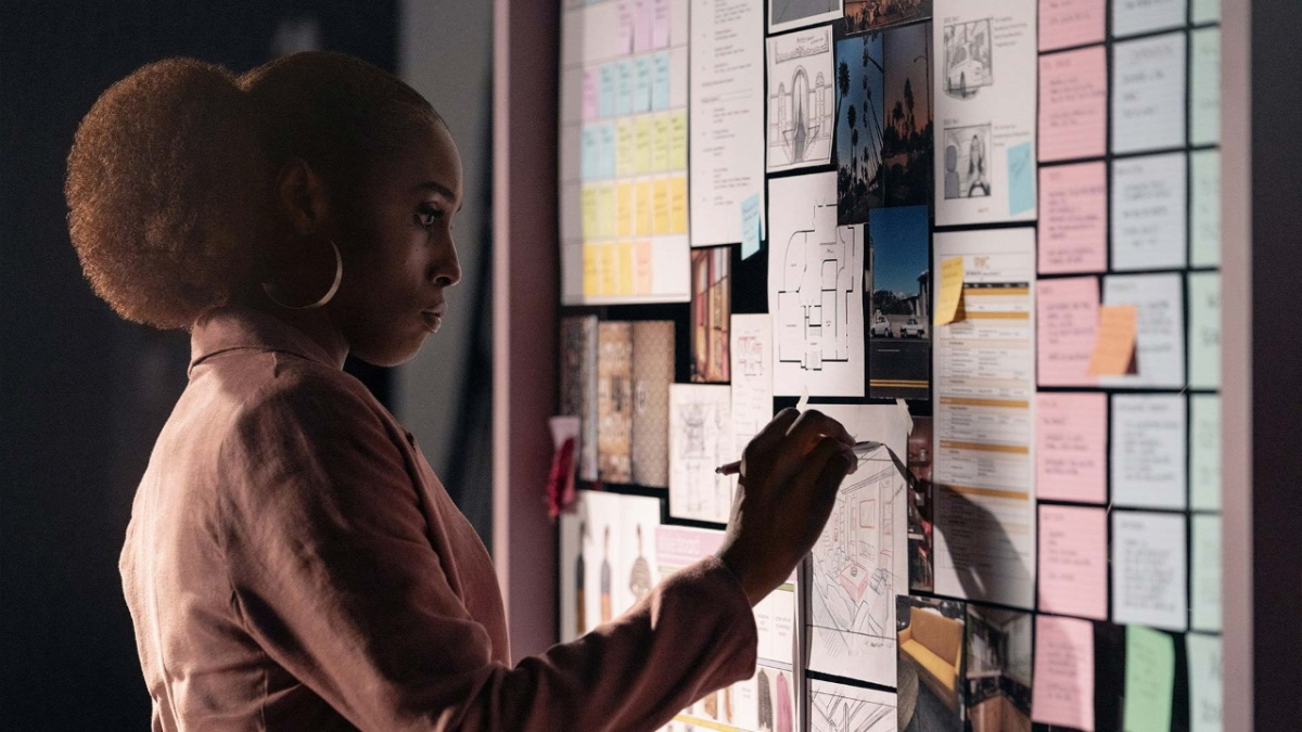 Actress Issa Rae stands before a wall covered with posted notes.