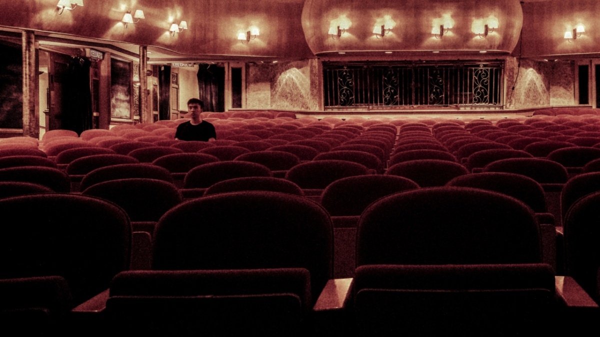 A man sits alone in a theater auditorium.