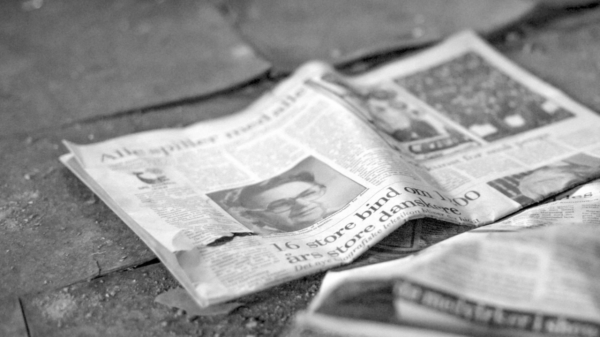A black and white photography of a newspaper placed upon the ground.
